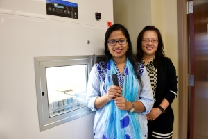 Farida Yasmin is standing in front of an environmental chamber. Dr. Song is standing beside Farida.
